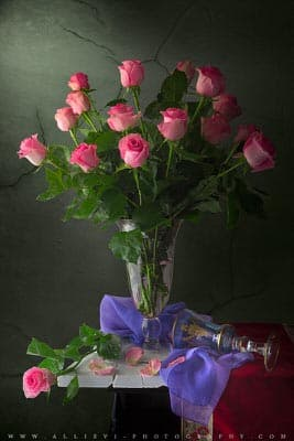 A still life photograph of roses blossoms in a glass vase.