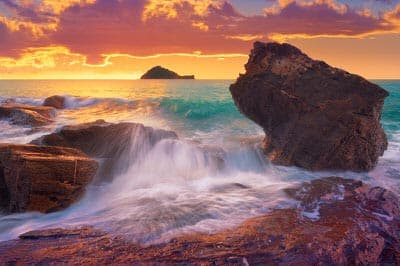 Waves splashing on the rocks at a beach at sunrise