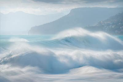 Waves crashing on a beach during a sea storm. High key seascape photo. Teal mint and white colors.